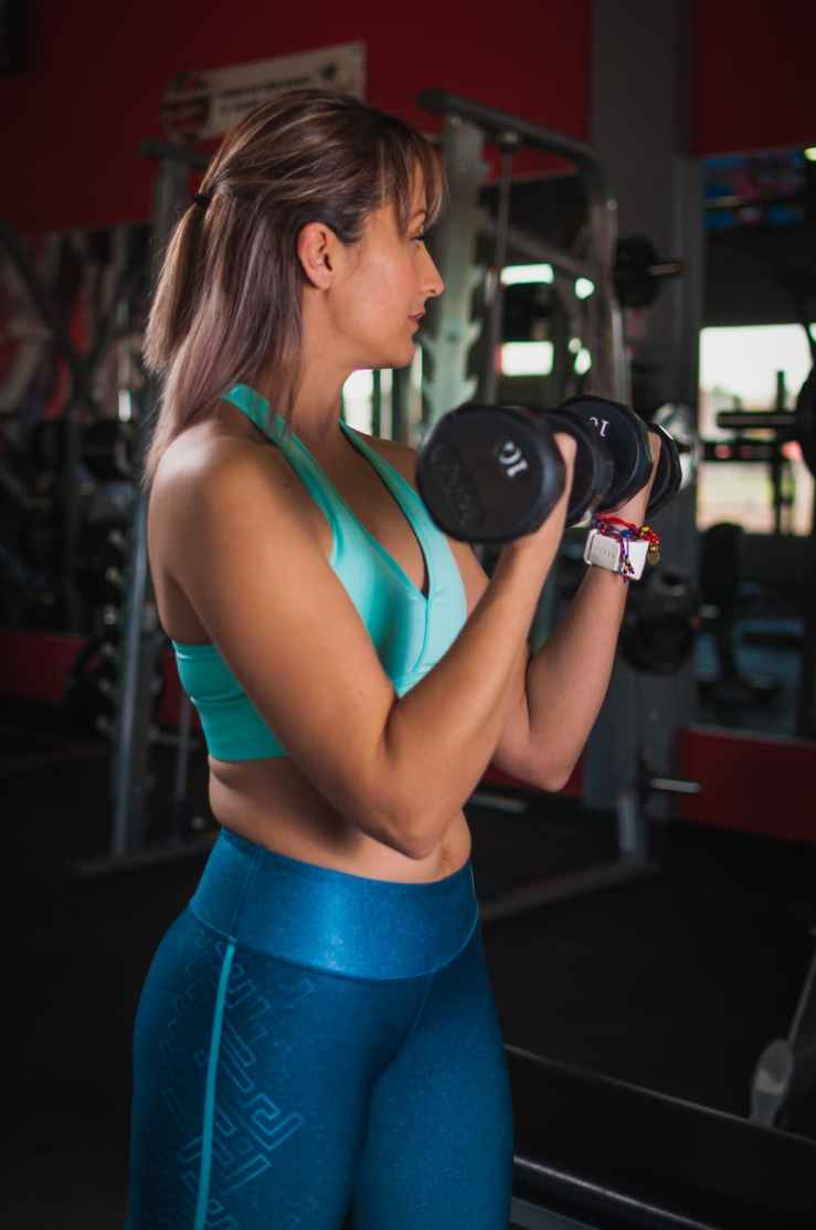 woman holding black dumbbells